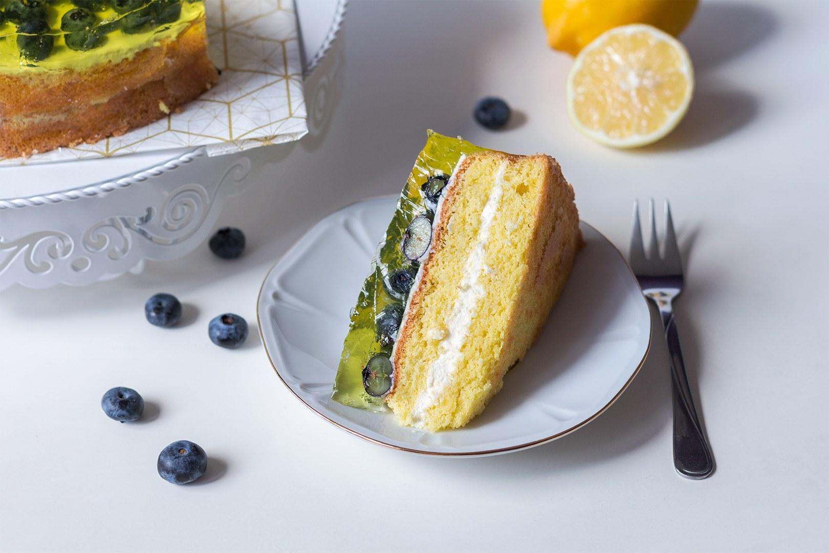 Descubre la receta de un refrescante bizcocho de mascarpone con un limón ligeramente agrio, quebrado con arándanos dulces.  Esta es una idea original para un pastel elegante para invitados: se ve muy bien en la mesa ... ¡y sabe muy bien!  Para hacer la receta utilicé un bizcocho desmontable Florina Likoris de 26 cm con fondo desmontable.  El pastel de limón y arándanos queda genial en el soporte metálico para pasteles Birmann Cake Couture, y sabe aún mejor en el plato de porcelana Mariapaula de la línea Gold Geometry.