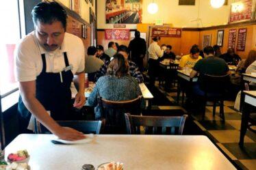 Camarero trabajando muchas horas en un restaurante